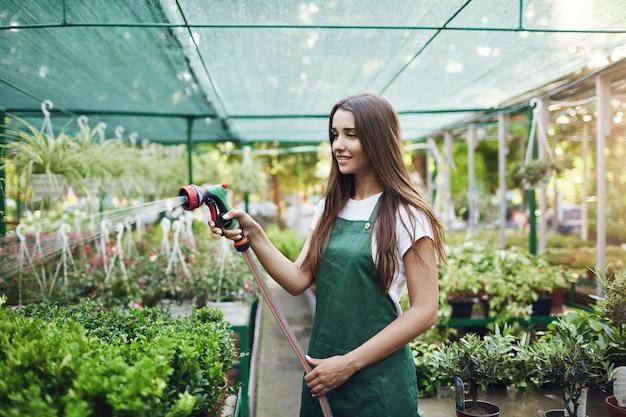 春の販売の準備をしている植物に水をまく若い庭の労働者