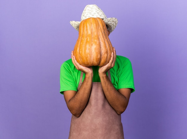 Young gardener afro-american guy wearing gardening hat holding and covered face with pumpkin