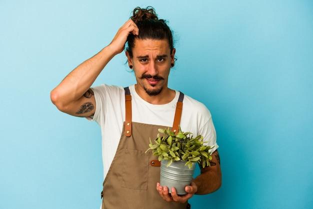青い背景に隔離された植物を持つ若い庭師の白人男性がショックを受け、彼女は重要な会議を思い出しました。