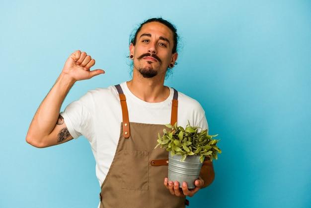 青い背景に植物を持つ若い庭師の白人男性は、誇りと自信を持って、従うべき例を示しています。
