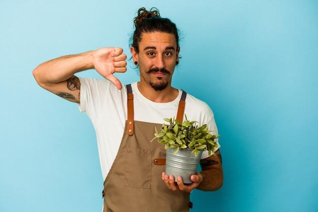 嫌なジェスチャーを示す青い背景に植物を保持している若い庭師の白人男性は、親指を下に向けます。不一致の概念。
