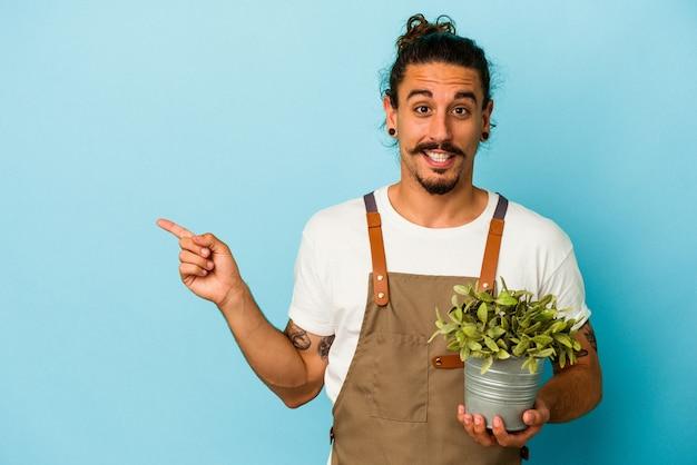 青い背景に分離された植物を保持している若い庭師の白人男性が笑顔でわきを指し、空白に何かを示しています。