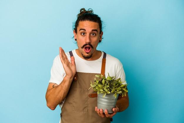 青の背景に分離された植物を保持している若い庭師の白人男性は、驚きとショックを受けました。