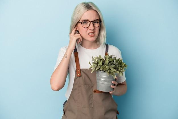 手で耳を覆う青い背景で隔離の植物を保持している若い庭師白人女性。