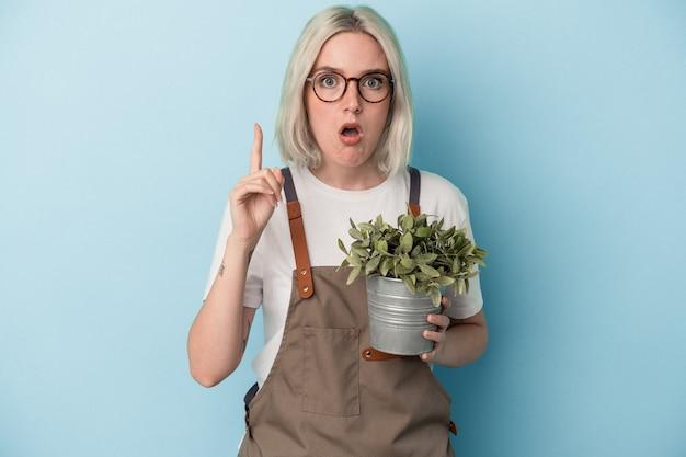 아이디어, 영감 개념을 가진 파란색 배경에 고립 된 식물을 들고 젊은 정원사 백인 여자.