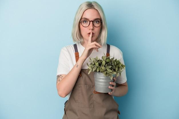 비밀을 유지하거나 침묵을 요구하는 파란색 배경에 고립 된 식물을 들고 젊은 정원사 백인 여자.