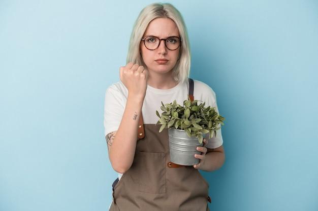 카메라에 주먹을 보여주는 파란 배경에 고립 된 식물을 들고 젊은 정원사 백인 여자, 공격적인 표정.
