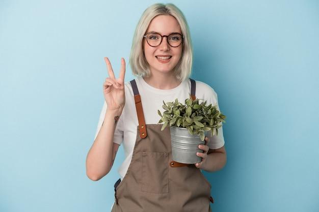 指で2番目を示す青い背景で隔離の植物を保持している若い庭師白人女性。
