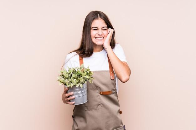 손으로 isolatedcovering 귀 공장을 들고 젊은 정원사 백인 여자.
