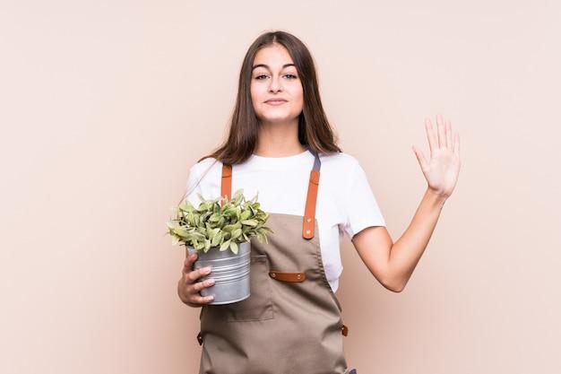 若い庭師白人女性が指で5つ植物を保持している陽気な陽気な表示数を笑っています。
