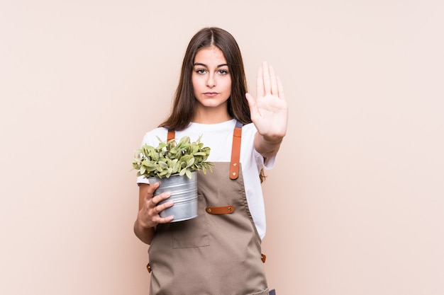 Young gardener caucasian woman holding a plant isolated standing with outstretched hand showing stop sign, preventing you.