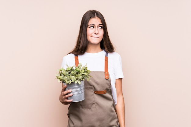 Young gardener caucasian woman holding a plant isolatedconfused, feels doubtful and unsure.
