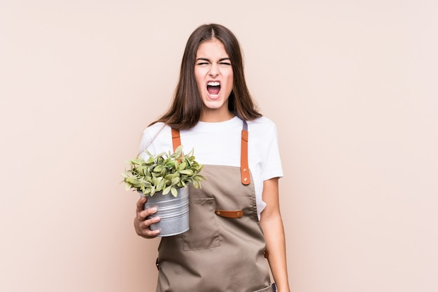 Young gardener caucasian woman holding a plant isolatedscreaming very angry and aggressive.