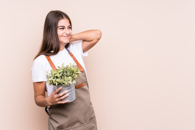 Young gardener caucasian woman holding a plant isolatedtouching back of head, thinking and making a choice.
