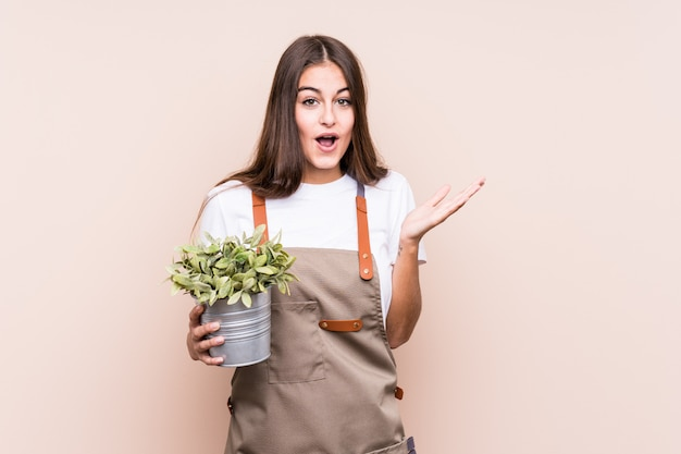 Young gardener caucasian woman holding a plant surprised and shocked.