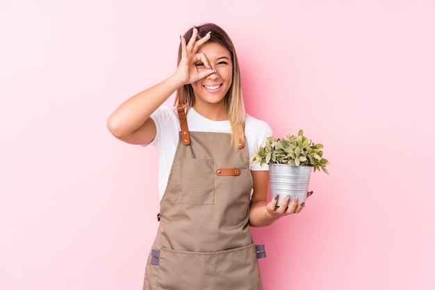 Young gardener caucasian woman isolated excited keeping ok gesture on eye.