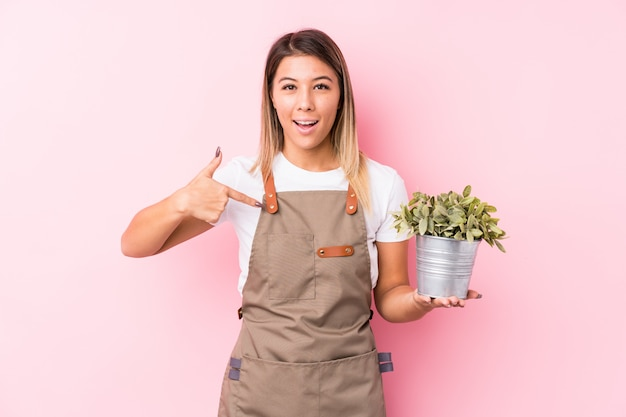 Young gardener caucasian woman isolated person pointing by hand to a shirt copy space, proud and confident