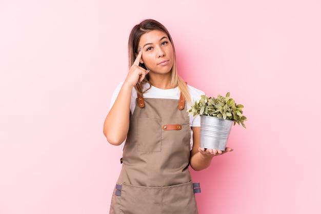 젊은 정원사 백인 여자는 작업에 초점을 맞춘 생각, 손가락으로 포인팅 사원 격리.