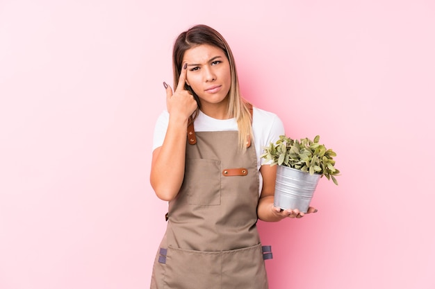 Young gardener caucasian woman isolated showing a disappointment gesture with forefinger.