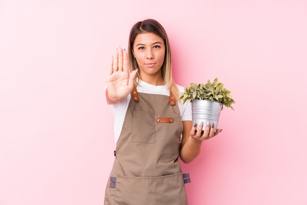 Young gardener caucasian woman isolated standing with outstretched hand showing stop sign, preventing you.