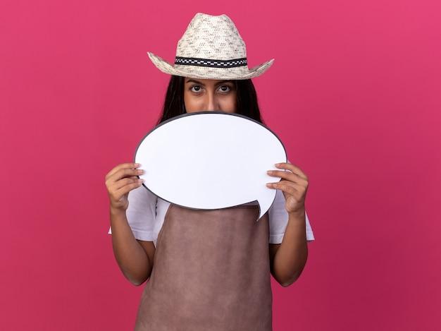 Giovane ragazza del giardiniere in grembiule e cappello estivo che tiene il segno in bianco della bolla di discorso davanti al suo fronte con la faccia seria che sta sopra la parete rosa