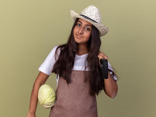 Giovane ragazza del giardiniere in grembiule e cappello estivo che tiene cavolo e pala con il sorriso sul viso in piedi sopra la parete verde