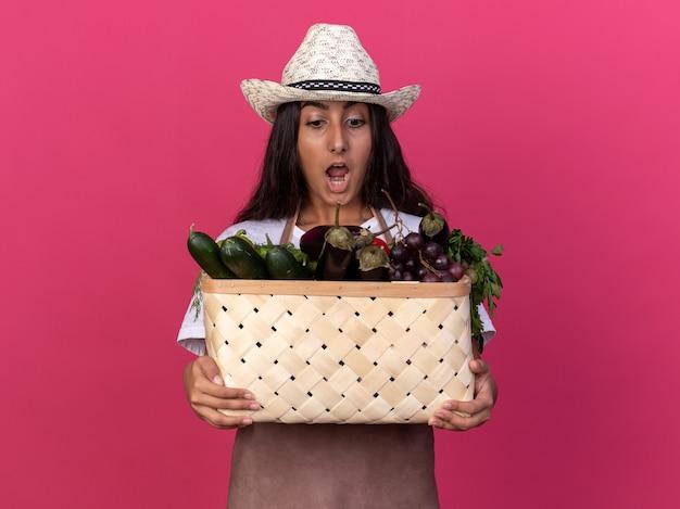 Giovane ragazza del giardiniere in grembiule e cappello estivo che tiene la cassa piena di verdure guardandoli stupiti e sorpresi in piedi sopra il muro rosa