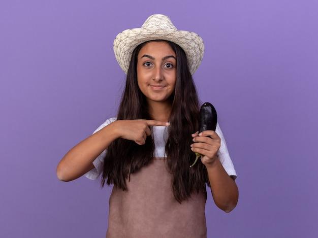 Giovane ragazza del giardiniere in grembiule e cappello estivo che tiene la melanzana che indica con il dito indice a sorridere felice e positivo che sta sopra la parete viola