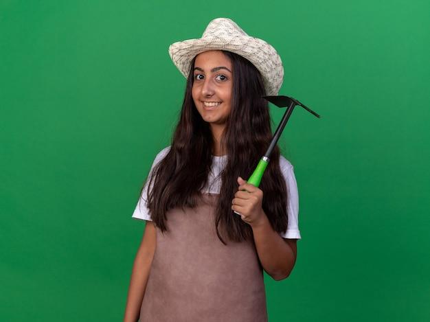 Giovane ragazza del giardiniere in grembiule e cappello estivo che tiene zappa sorridente felice e allegro in piedi sopra la parete verde