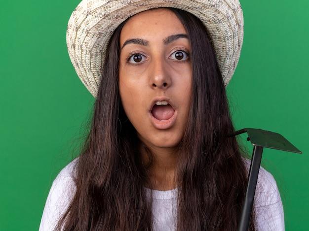 Ragazza giovane giardiniere in grembiule e cappello estivo azienda zappa sorpreso in piedi sopra la parete verde
