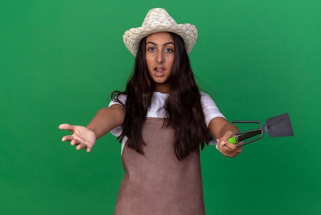 Giovane ragazza del giardiniere in grembiule e cappello estivo che tiene le mani di ampia apertura del mattock sorpreso in piedi sopra la parete verde