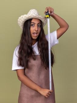 Giovane ragazza del giardiniere in grembiule e cappello estivo che tiene nastro di misura felice e sorpreso in piedi sopra la parete verde