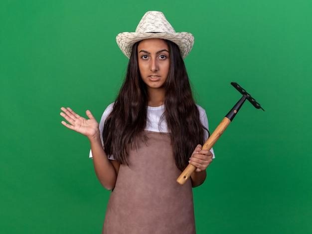 Giovane ragazza del giardiniere in grembiule e cappello estivo che tiene il mini rastrello confuso e incerto che alza il braccio che sta sopra la parete verde