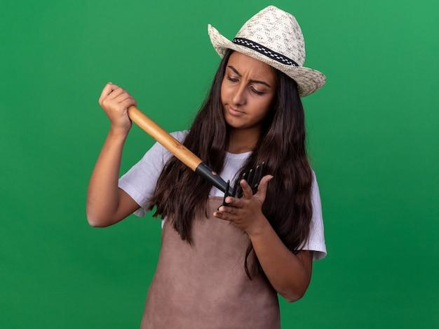 Ragazza giovane giardiniere in grembiule e cappello estivo che tiene mini rastrello guardando con faccia seria in piedi sopra la parete verde
