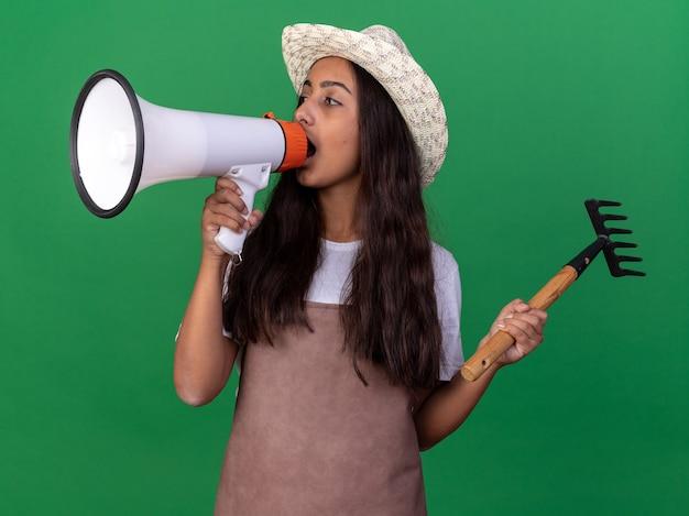 Giovane ragazza del giardiniere in grembiule e cappello estivo che tiene mini rastrello che grida al megafono che sta sopra la parete verde