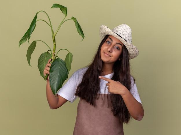 Giovane giardiniere ragazza in grembiule e cappello estivo azienda pianta che punta con il dito indice sorridendo fiducioso in piedi sopra la parete verde