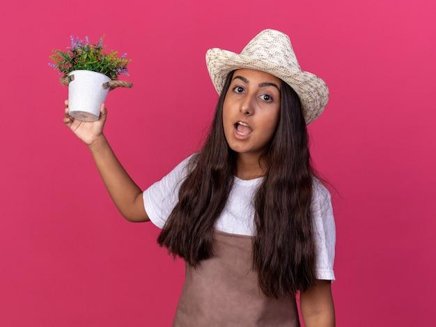 Giovane ragazza del giardiniere in grembiule e cappello estivo che tiene pianta in vaso sorpreso in piedi sopra la parete rosa