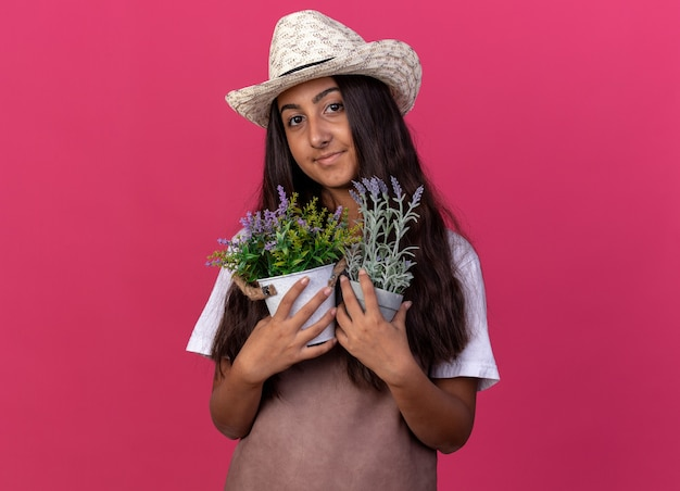 Giovane ragazza del giardiniere in grembiule e cappello estivo che tiene le piante in vaso che sorridono con la faccia felice che sta sopra la parete rosa