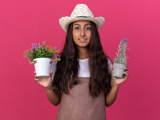 Young gardener girl in apron and summer hat holding potted plants  smiling with happy face standing over pink wall
