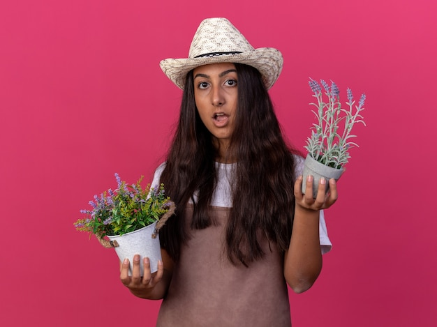 Young gardener girl in apron and summer hat holding potted plants  surprised and amazed standing over pink wall