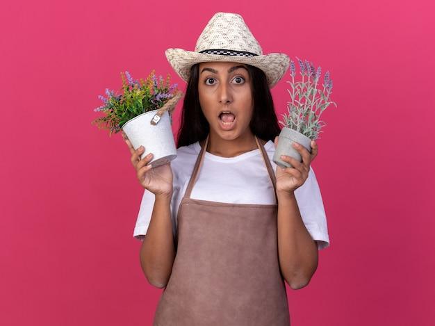 Giovane ragazza del giardiniere in grembiule e cappello estivo che tiene le piante in vaso sorprese in piedi sopra la parete rosa