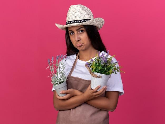 Giovane ragazza del giardiniere in grembiule e cappello estivo che tiene piante in vaso con espressione triste che fa la bocca ironica in piedi sopra il muro rosa
