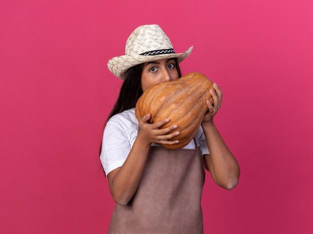 Ragazza giovane giardiniere in grembiule e cappello estivo tenendo la zucca davanti al viso in piedi sopra il muro rosa