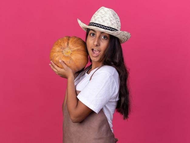 Giovane ragazza del giardiniere in grembiule e cappello estivo che tiene zucca felice ed emozionato in piedi sopra la parete rosa