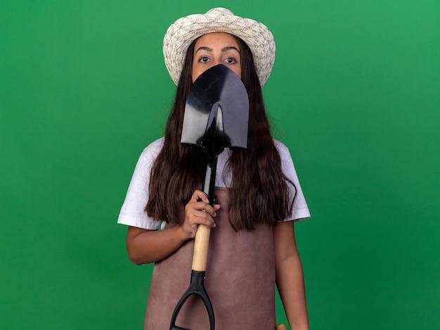 Ragazza giovane giardiniere in grembiule e cappello estivo tenendo la pala davanti al viso in piedi sopra la parete verde