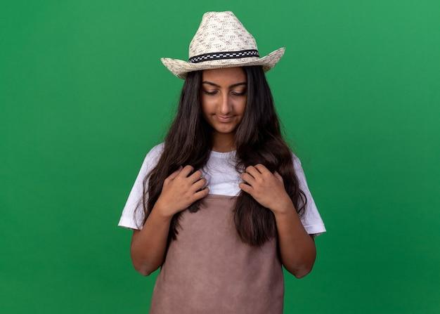 Ragazza giovane giardiniere in grembiule e cappello estivo guardando verso il basso con le mani sul petto in piedi sopra la parete verde