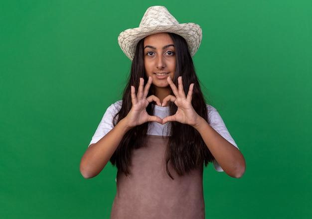 Ragazza giovane giardiniere in grembiule e cappello estivo che fa il gesto del cuore con il sorriso sul viso in piedi sopra la parete verde