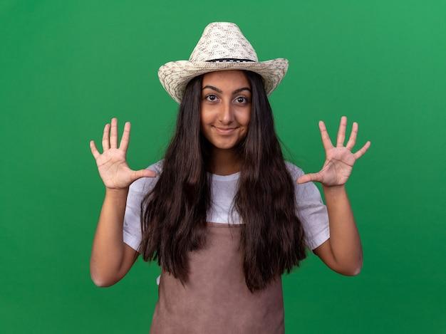 Ragazza giovane giardiniere in grembiule e cappello estivo sorridendo allegramente mostrando apre le palme in piedi sopra la parete verde