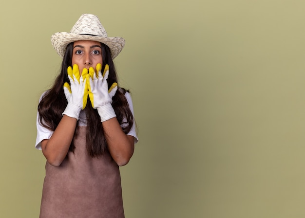 Giovane giardiniere ragazza in grembiule e cappello estivo indossando guanti da lavoro essendo scioccato che copre la bocca con le mani in piedi sul muro verde