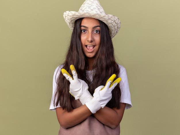 Giovane ragazza del giardiniere in grembiule e cappello estivo che indossa guanti da lavoro mani felici e allegre che attraversano le mani che mostrano il segno di v che sta sopra la parete verde